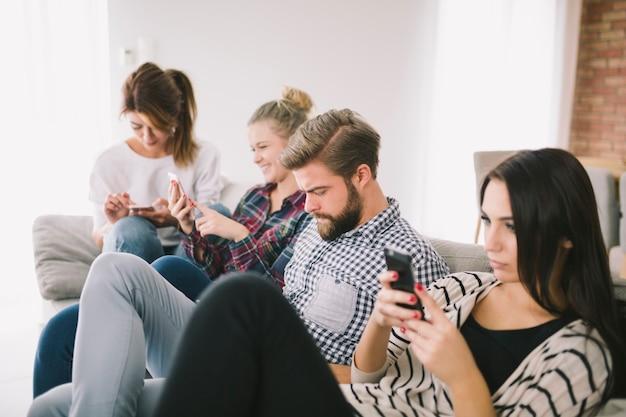 ソファに座っている電話に執着している人々