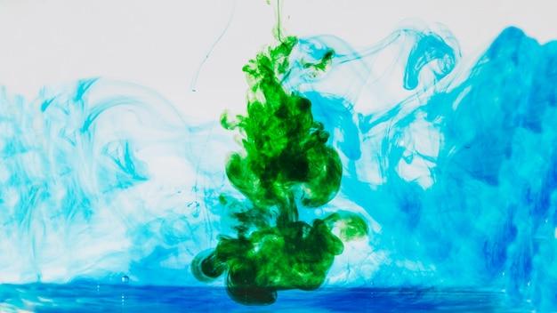 Зеленый краситель, пролитый в синий цвет