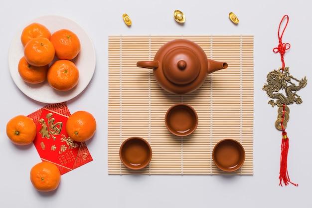 タンジェリンと中国の装飾の近くに置かれたお茶