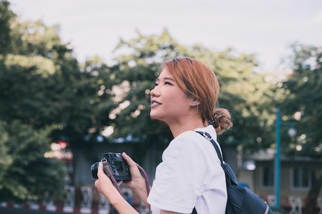 都市の写真を撮っているカジュアルな女性