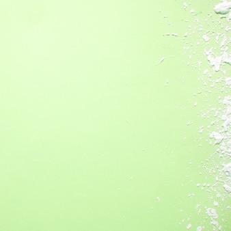 柔らかい緑色の上にこぼれた白い塗料