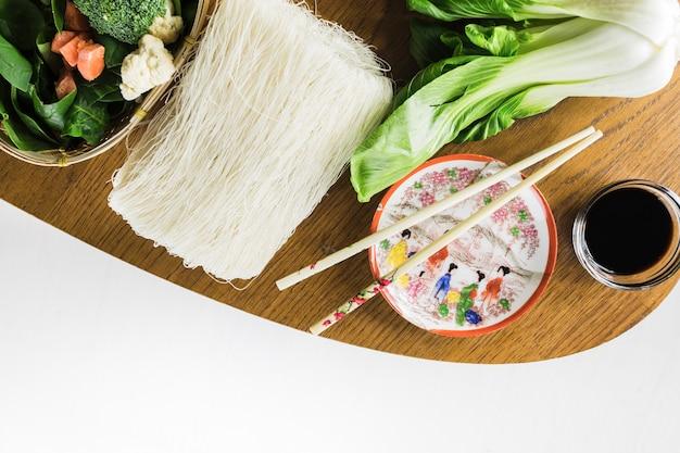 Палочки для еды рядом с лапшой и овощами