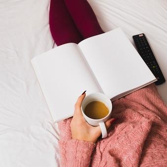コーヒーとノートブックでリラックスした女性作物