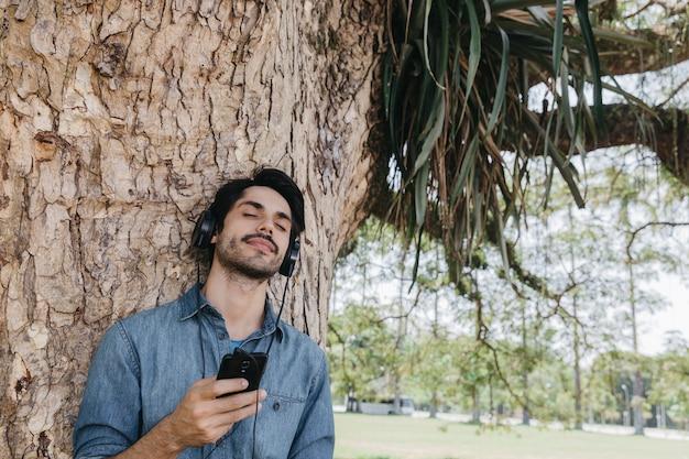 Мечтающий человек, наслаждающийся музыкой в парке