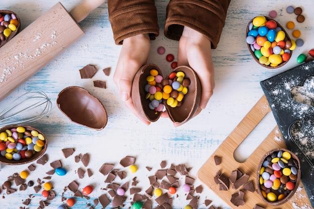 チョコレートの卵を開く作物の手