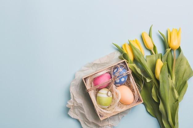 青いチューリップの近くに卵がある箱