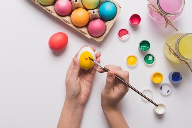 Обрезать руки, рисуя цыпленка на яйце