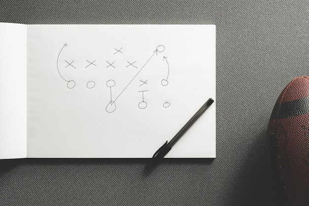Американский футбольный мяч рядом с стратегией игры