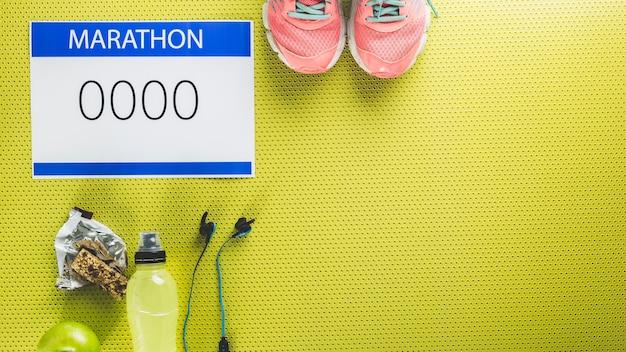 Номер марафона рядом с кроссовками и водой