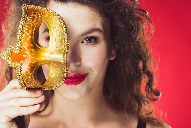 黄金のマスクで笑顔の大人の女性