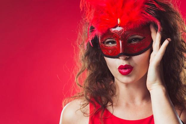 赤いマスクの中に立っている大人の女性