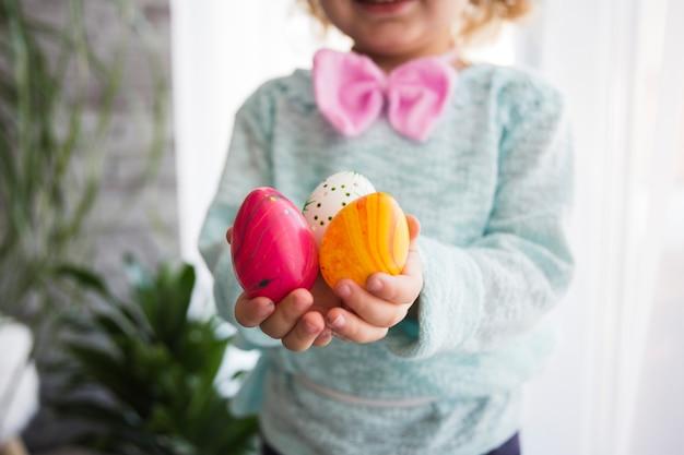 Урожай девочка показывает пасхальные яйца