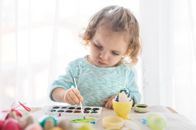 愛らしい子供が卵を描く