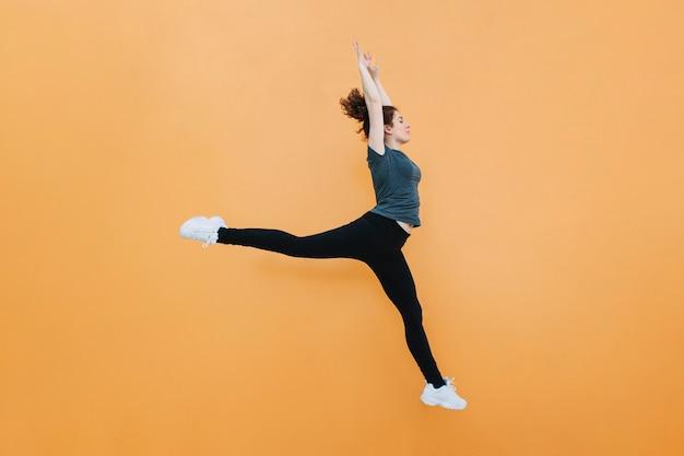 黄色の壁でジャンプするスポーティな女性