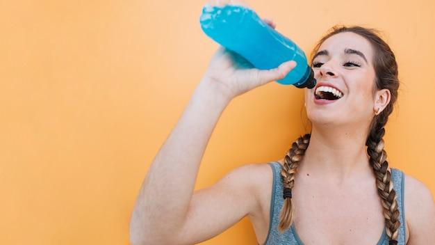 青い飲み物を持つスポーティーな女性