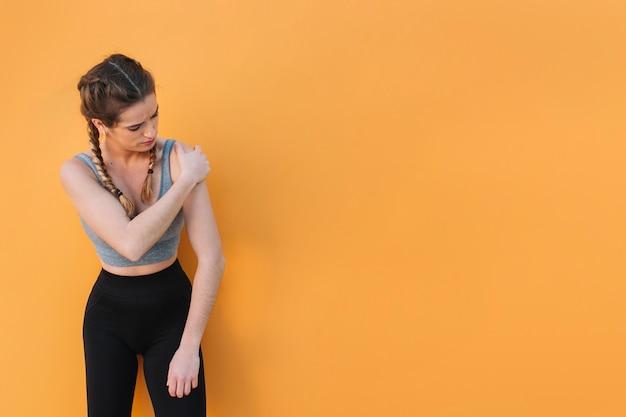 Женщина, касаясь травмированного плеча