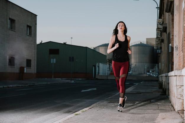 Уверенная спортсменка, бегущая по улице
