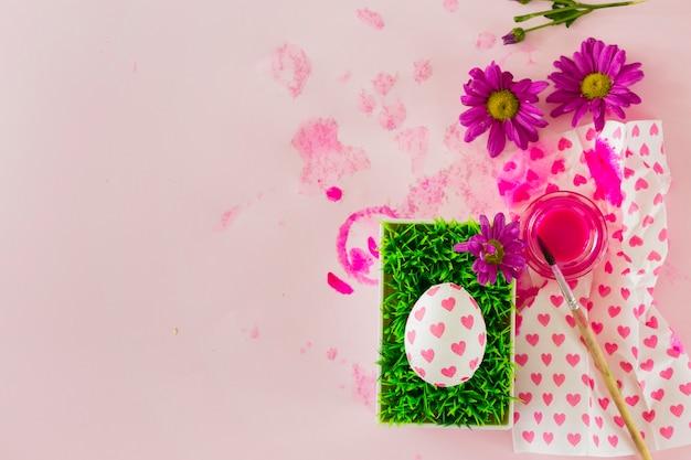 Яйцо на траве возле краски и цветов