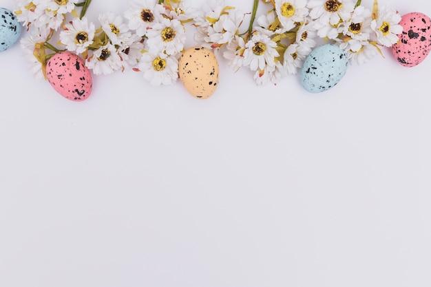 花の近くの色付きのイースターエッグ