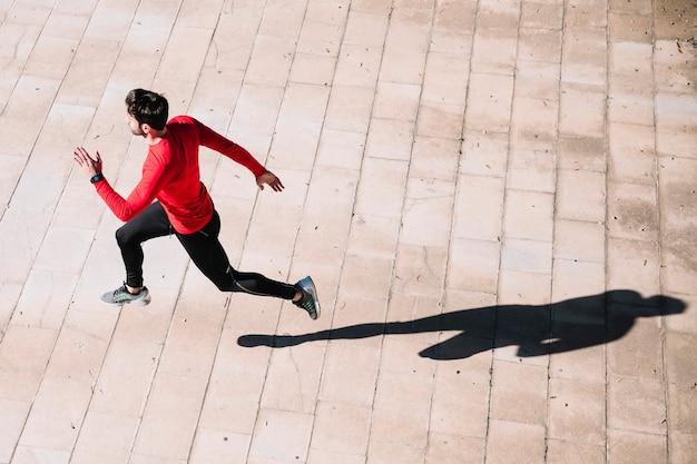 Сверху человек прыгает на тротуар