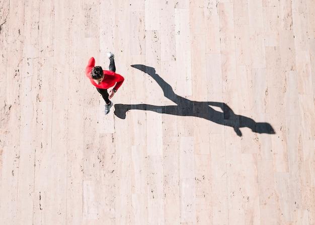 Сверху спортсмен работает на тротуаре