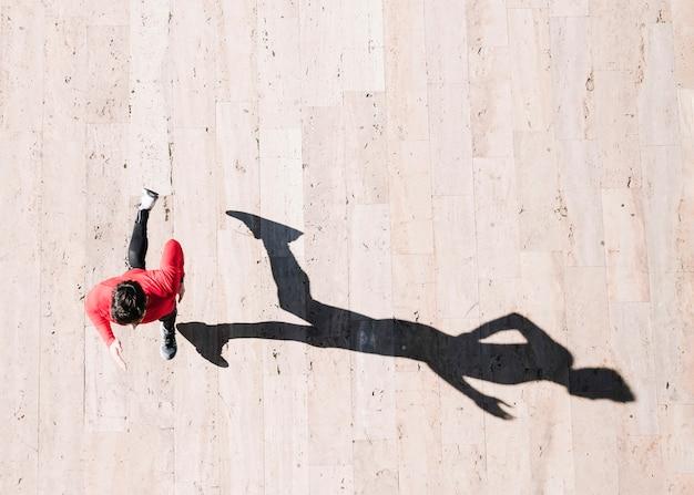 Сверху спортсмен бежит по тротуару