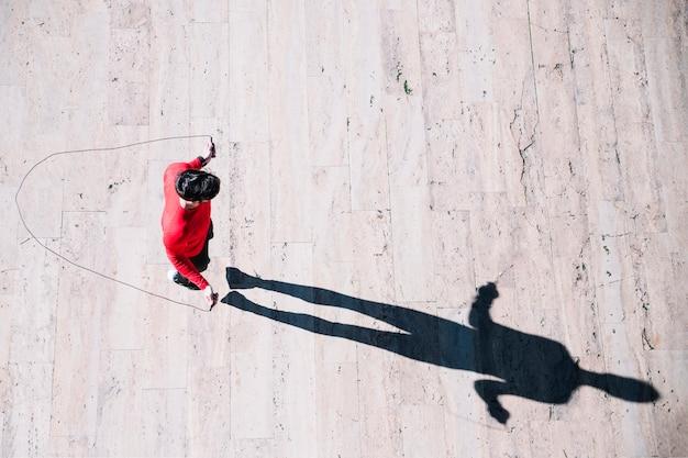 Сверху спортсменка прыгающая веревка