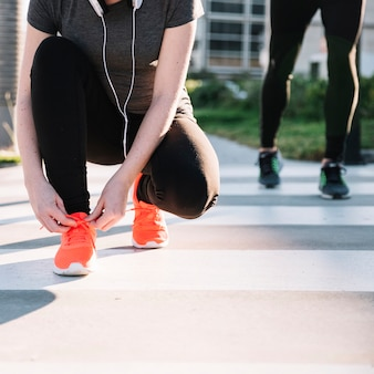 手作りの女性がスニーカーに靴ひもを結ぶ