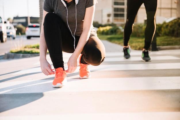 トレーニングで靴ひもを結ぶ女性作物