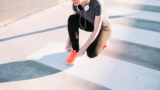 横断歩道で靴ひもを結ぶ作物の女性