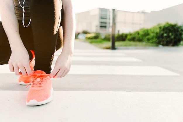 スポーツシューズで靴ひもを結ぶ女性作物