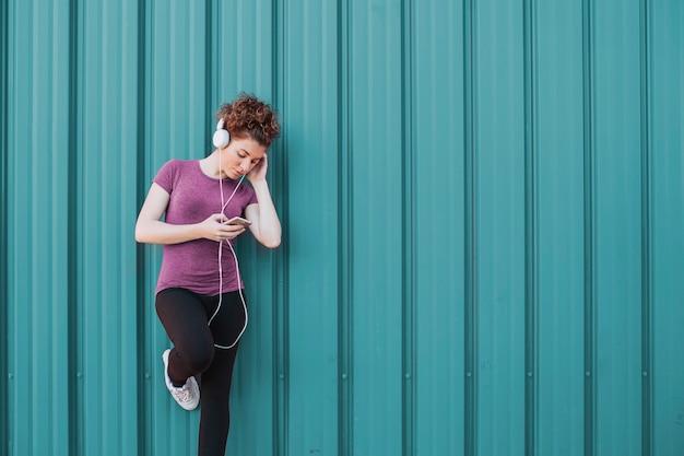 Спортсменка с наушниками и телефоном на улице