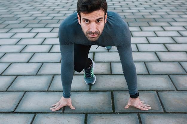 Определенный спортсмен на корточках