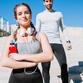 Уверенная спортивная девушка и мужчина на улице