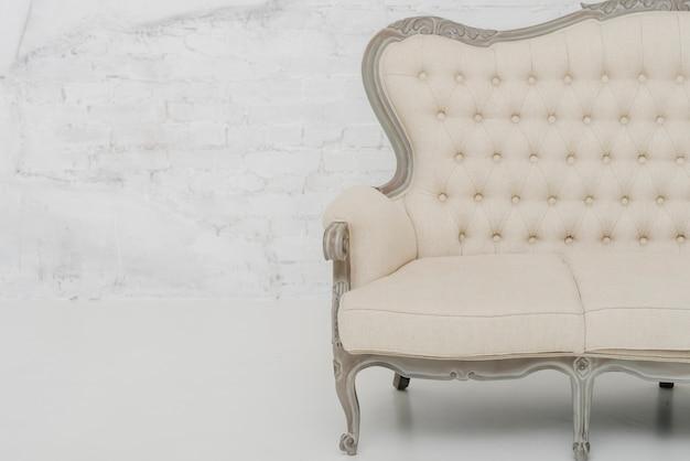 白い壁の近くの快適なソファー