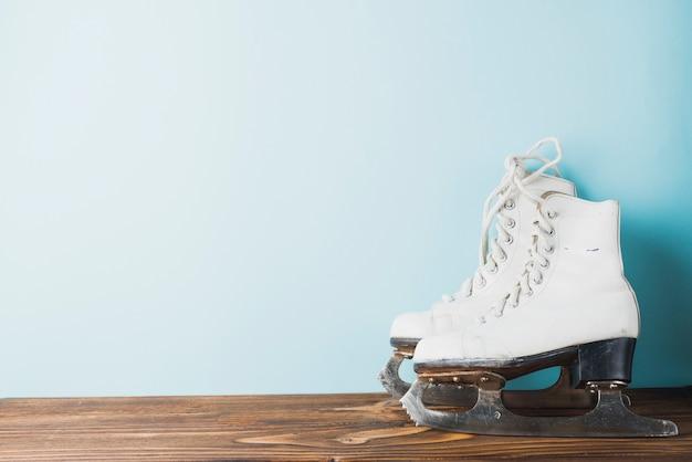 Ледяные коньки возле синей стены