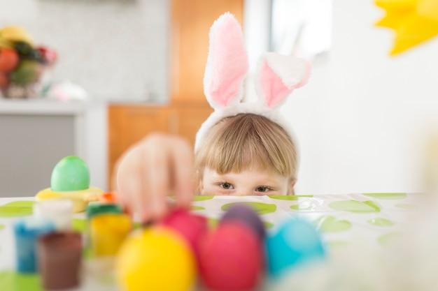 Девушка берет яйцо для рисования