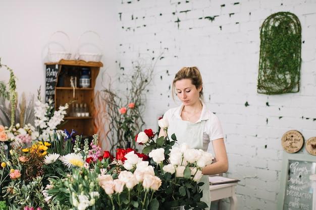 花屋はテーブルで花束を作る