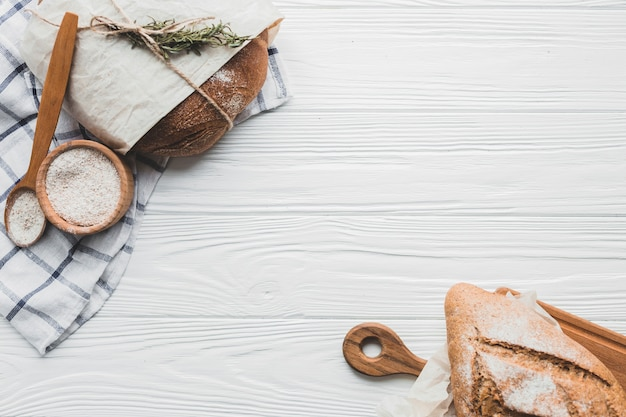 Вкусные булочки с хлебом на деревянном столе