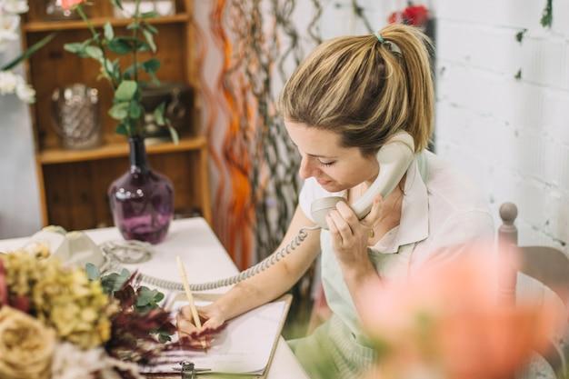 電話で話してノートを書く花屋