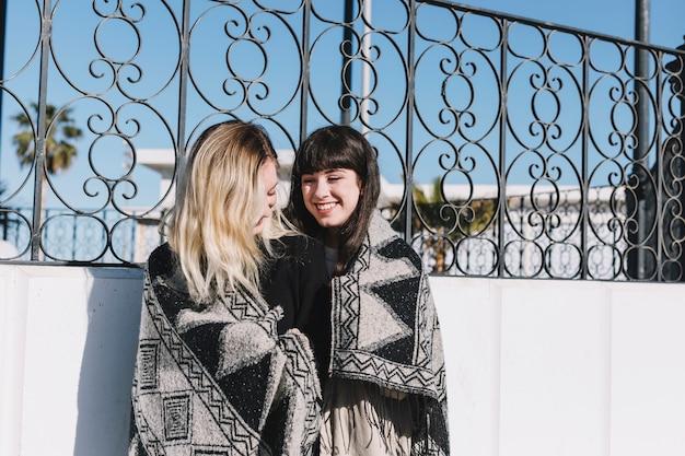 Молодые симпатичные подружки обнимаются в плед