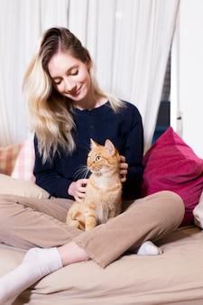 かなりの金髪の猫と座っている