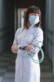 Женщина-медик в маске со стетоскопом