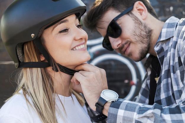 Красивый мужчина, закрепляющий шлем на женщине