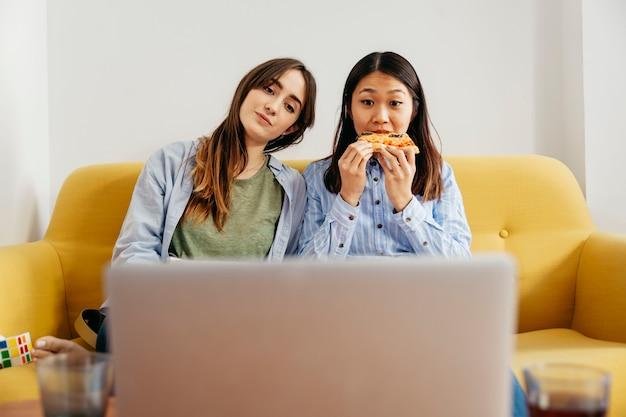 Расслабляющие девушки смотрят фильм, питая пиццу