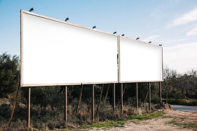 Пустые белые рекламные щиты на пригородной дороге