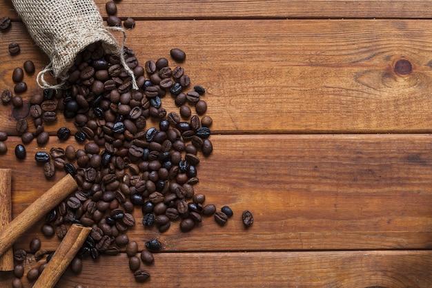 こぼれたコーヒー豆の近くのシナモン