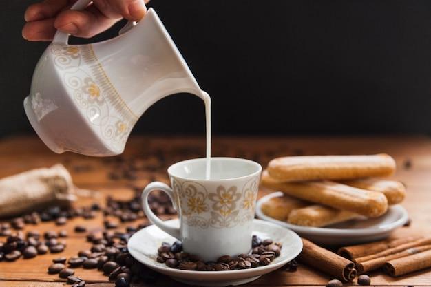 Кастрюля, наливающая молоко в чашку