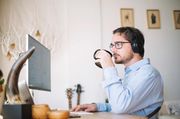 コンピュータと飲み物で働く男