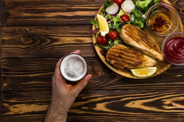 Рука пива рядом с курицей и салатом